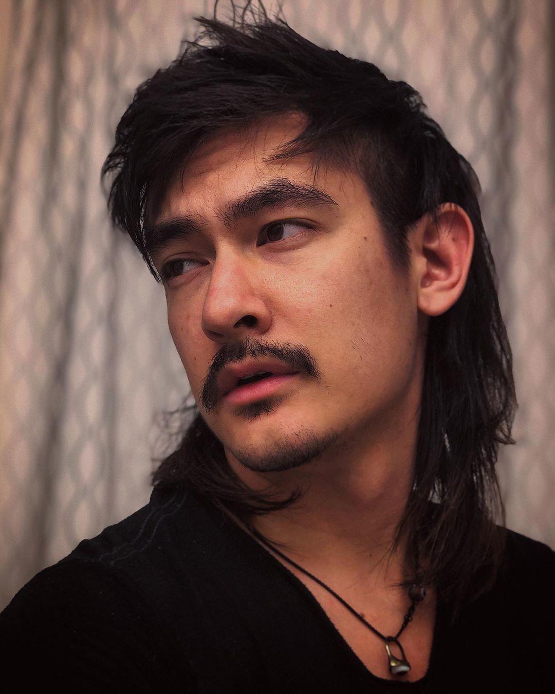 Un homme aux cheveux foncés dans une coupe de mulet long