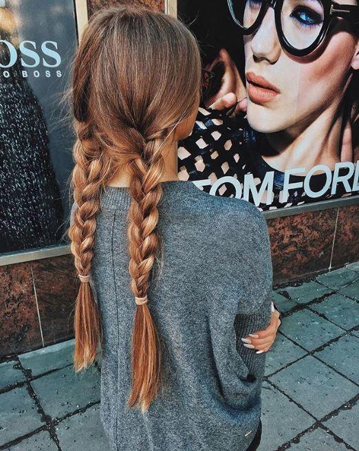 Coiffures pour cheveux longs et fins : Femme aux longs cheveux bruns et raides en nattes tressées, portant un pull tricoté gris foncé.
