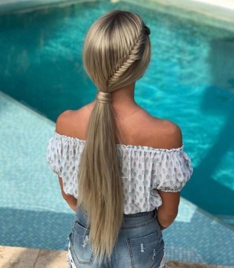Coiffures pour cheveux longs et fins : Femme blonde avec une longue queue de cheval française en queue de poisson, assise au bord d'une piscine et portant une tenue d'été.