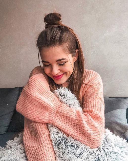 Coiffures pour cheveux longs et fins : Femme aux cheveux bruns raides, coiffée en chignon mi-hauteur, mi-dessous, portant un pull en tricot rose au lit.