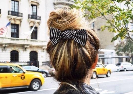 Coiffures pour cheveux longs et fins : Femme blonde aux cheveux en chignon avec un accessoire en forme de noeud dans la rue de New York.