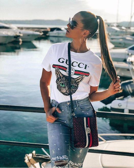 Coiffures pour cheveux longs et fins : Femme aux longs cheveux lisses brun clair en queue de cheval haute et lisse qui se tient aux extrémités de ses cheveux, portant un top logo et un jean.