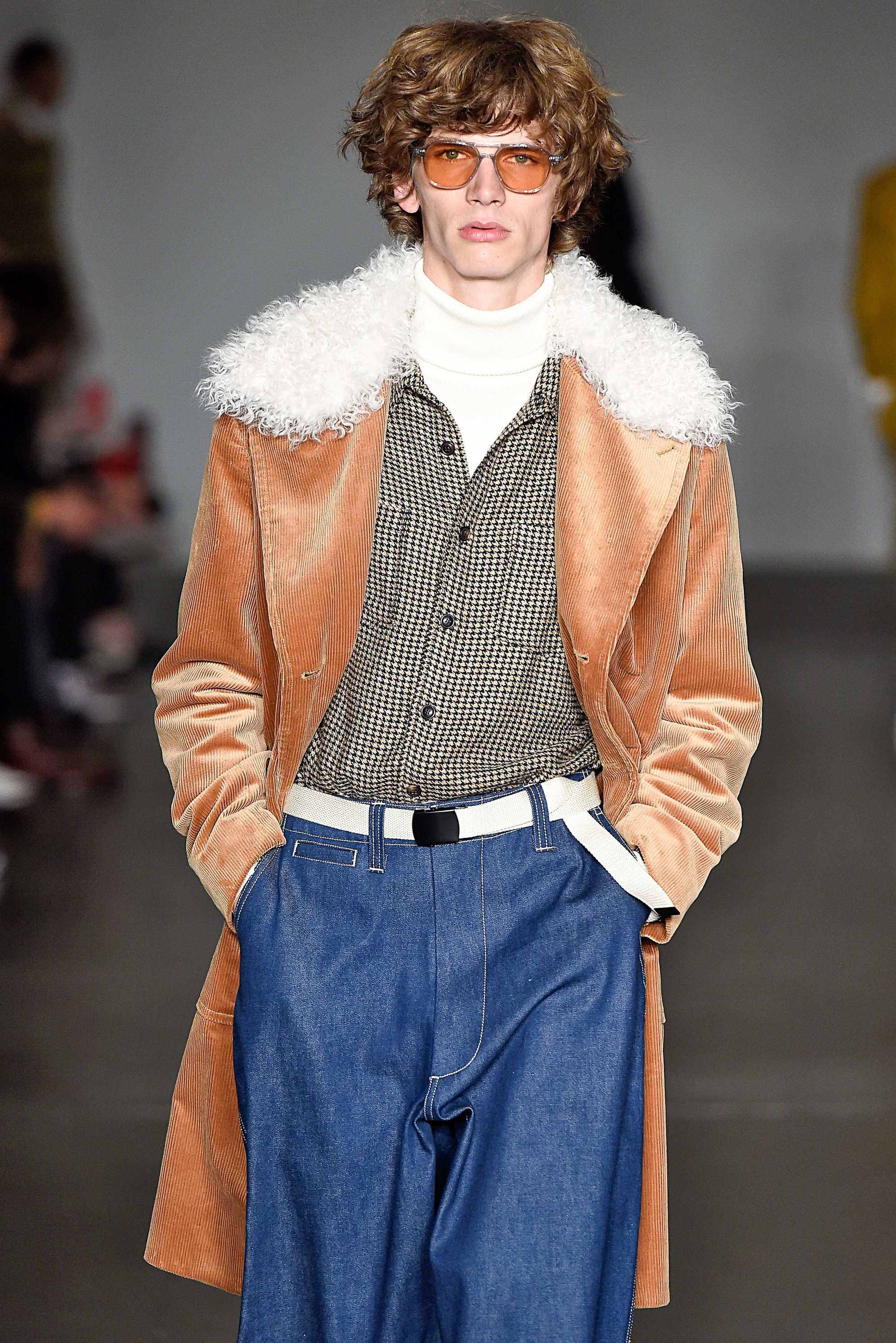 modèle masculin sur la piste de todd snyder fw18 avec des cheveux bouclés de longueur moyenne brun doré