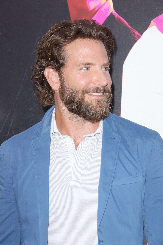 bradley cooper long cheveux bruns épais et ondulés, repliés derrière les oreilles et portant une longue barbe