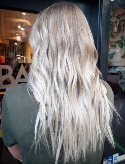 Vue de dos d'une femme aux longs cheveux d'ombre blond clair ébouriffés