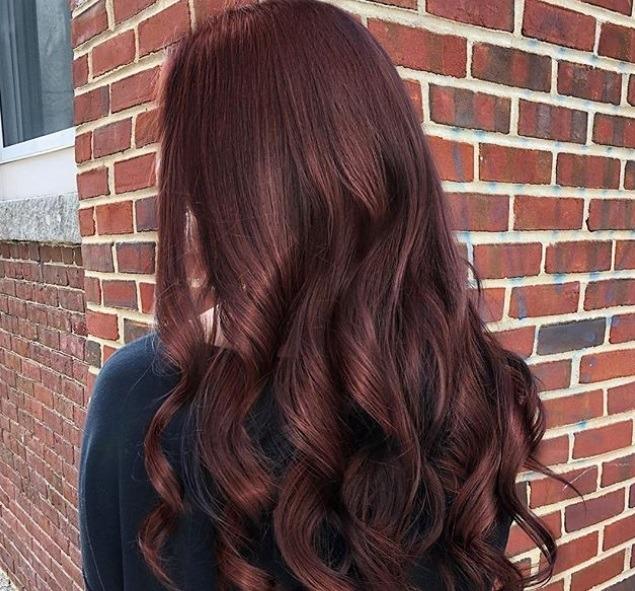 Cheveux bruns roux : Plan de dos d'une femme aux cheveux longs roux et bruns, coiffés en boucles lâches.