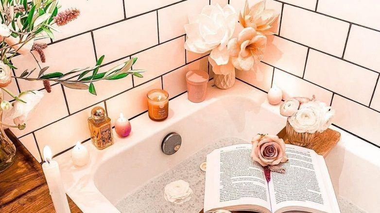 Photo d'un bain avec des bougies relaxantes et un livre