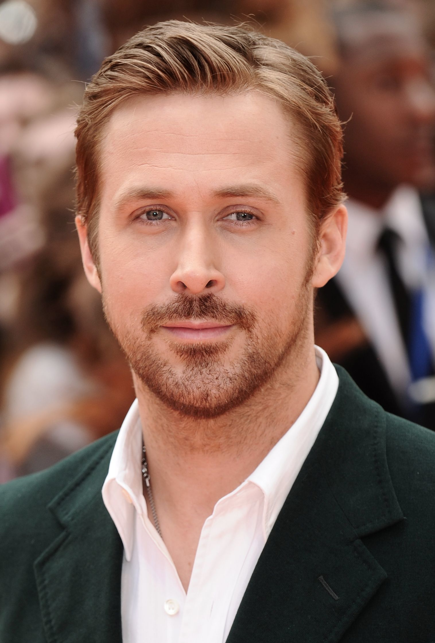 Coupe de cheveux de Ryan Gosling : Ryan Gosling avec une coupe de cheveux et une barbe en peigne, portant un costume vert