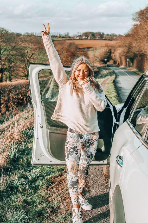 Journée internationale de la femme : l'autonomisation : Em Sheldon devant la portière d'une voiture ouverte, donnant un signe de paix