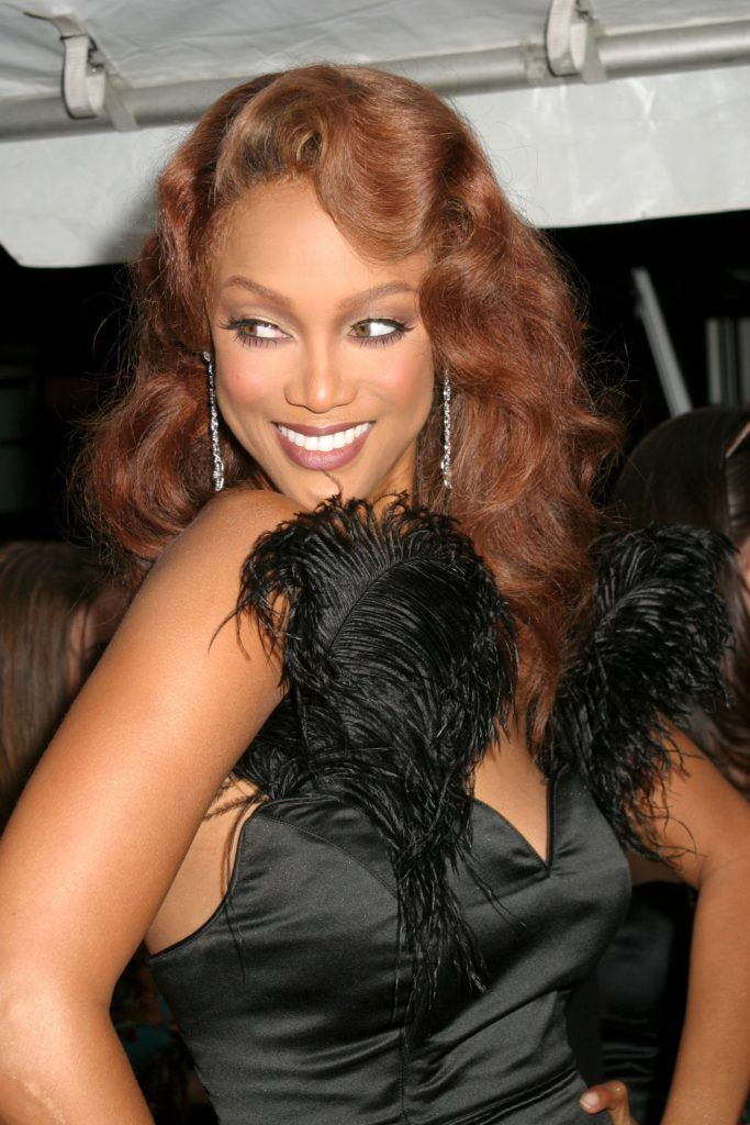 Tyra Banks avec des cheveux roux en boucles latérales rétro