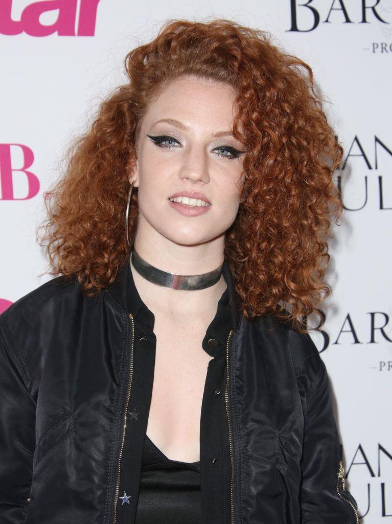 Jess Glyne avec des cheveux roux et une grosse permanente bouclée