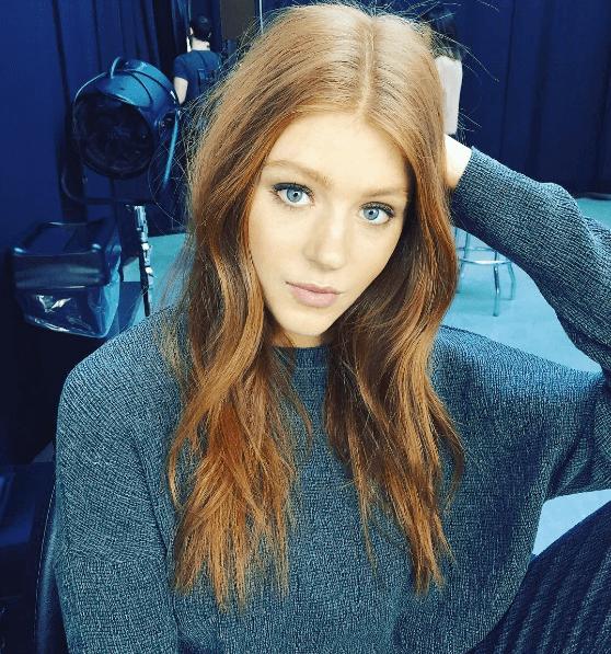 modèle avec des cheveux roux et une raie centrale soignée
