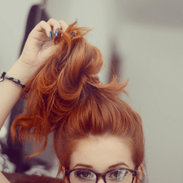 femme de couleur roux tirant ses cheveux en un nœud supérieur