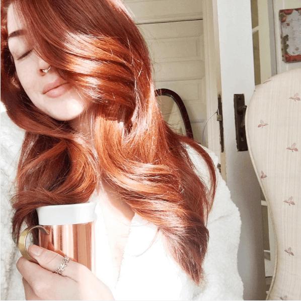 femme avec de grandes boucles et des cheveux roux cuivrés brillants