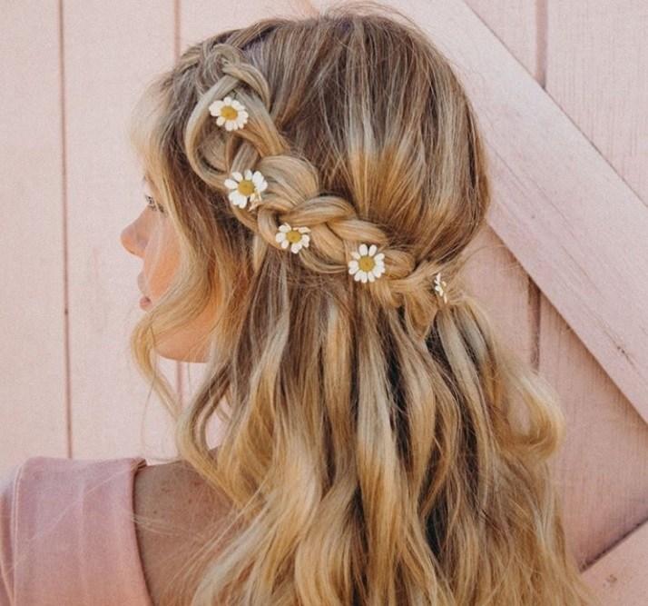 les coiffures de bal de fin d'année : plan arrière d'une femme blonde avec une tresse mi-haute, mi-dessous avec des fleurs de marguerite tissées dedans, portant un haut rose