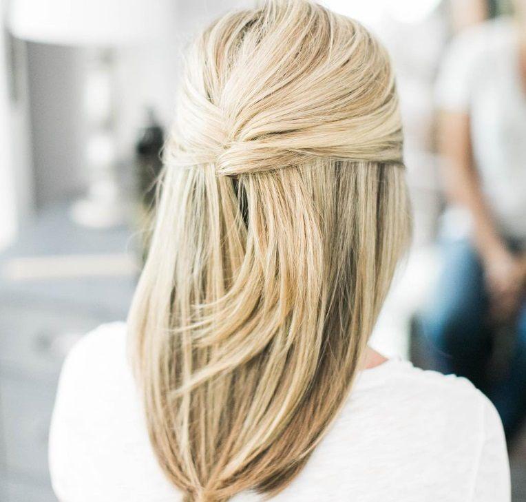 Coiffures de bal mi-hautes, mi-bas : gros plan d'une femme aux cheveux blonds de longueur moyenne, façonnés en demi-lune française