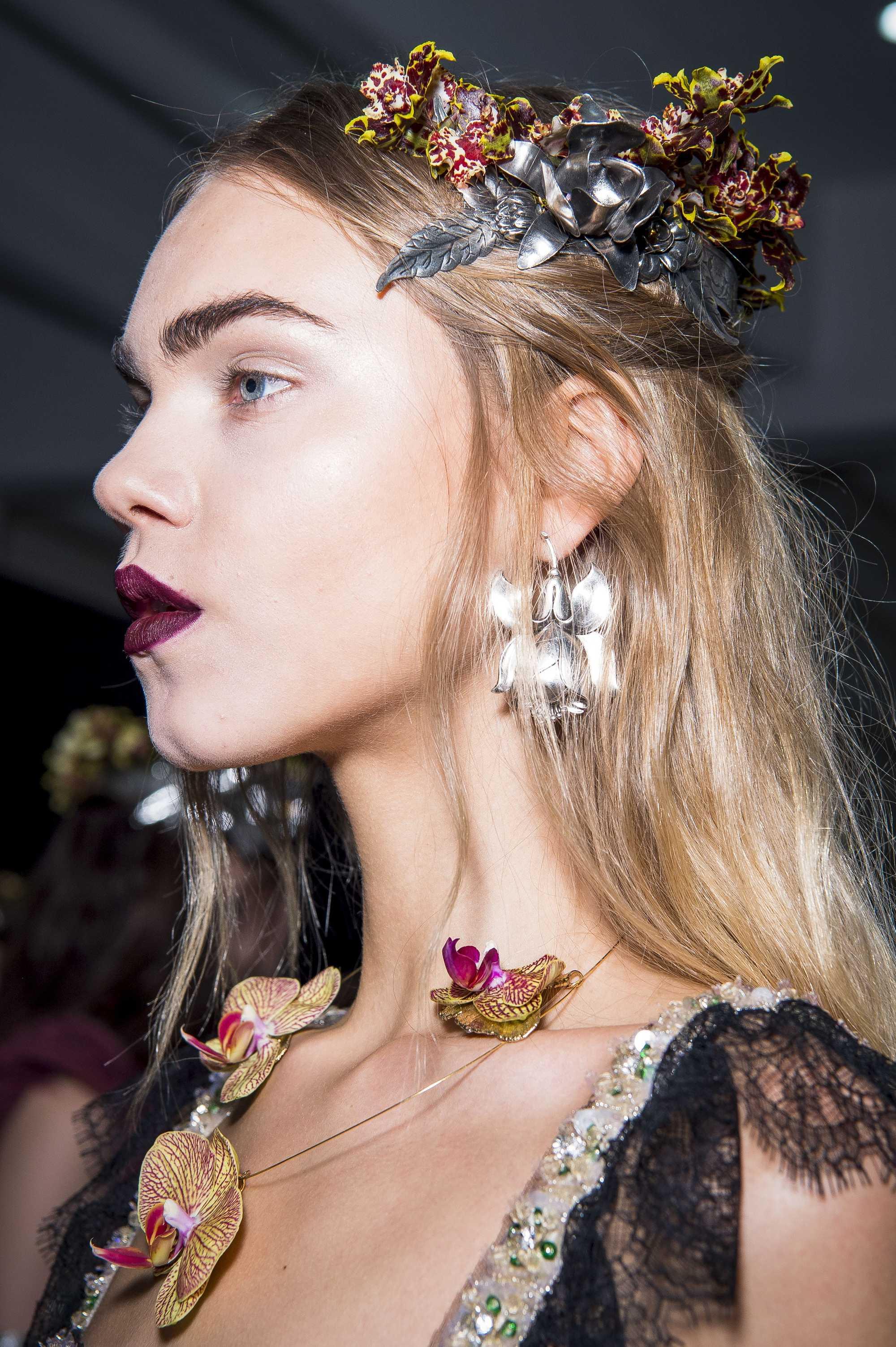 gros plan du modèle avec une coiffure à moitié haute avec des pinces à fleurs dans les coulisses de Rodarte