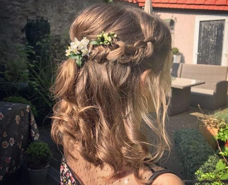 les coiffures de bal de fin d'année : gros plan d'une femme aux cheveux bruns coiffée en une tresse lâche, mi-haute, mi-basse, avec des fleurs