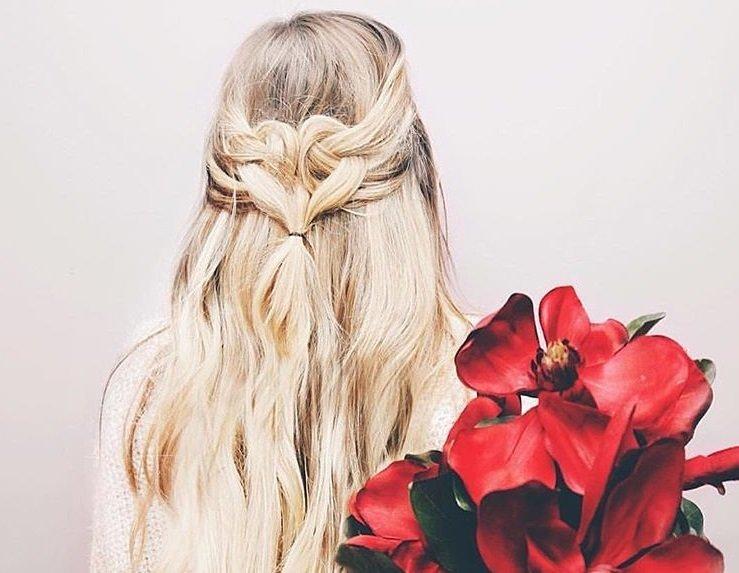 Coiffures de bal de fin d'année : plan arrière d'une femme aux cheveux blond platine coiffée en boucle de cœur à moitié relevé, tenant des fleurs et posant sur un fond blanc