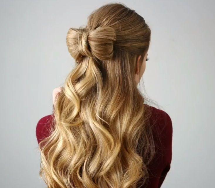 les coiffures de bal de fin d'année : plan arrière d'une femme aux cheveux blonds dorés, coiffée d'une coiffure ondulée, mi-haute, mi-basse, portant un haut rouge et posant dans un décor de studio