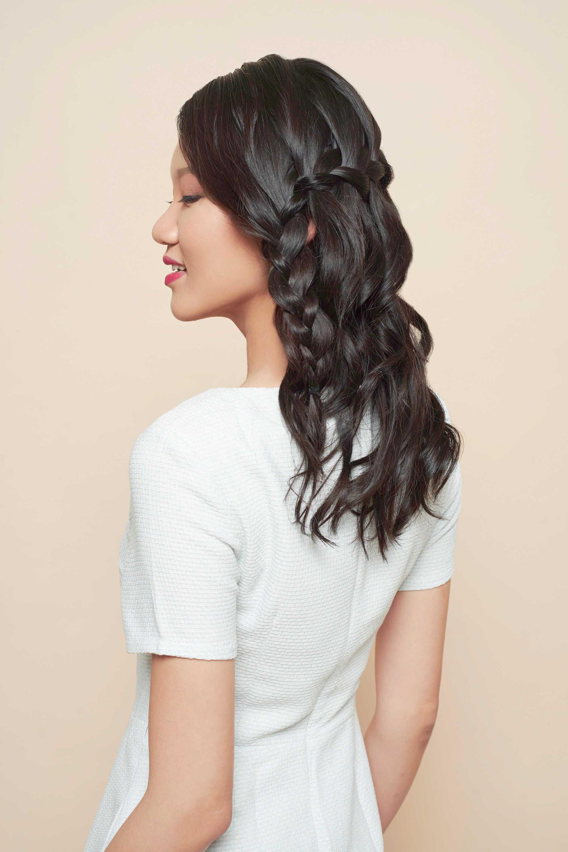Coiffures de bal de fin d'année : gros plan d'un mannequin aux cheveux châtain foncé coiffé en tresse de cascade, portant une robe blanche et posant dans un studio