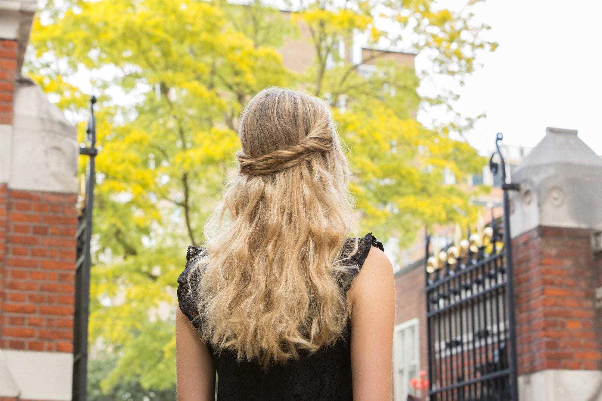 idées de coiffure pour le bal de fin d'année : gros plan arrière d'une femme aux cheveux blonds dorés ondulés, coiffée en une coiffure torsadée, mi-haut, mi-bas, portant une chemise noire et posant à l'extérieur