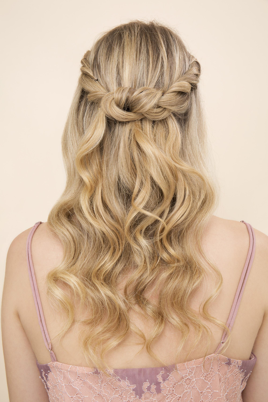 idées de coiffure pour le bal de fin d'année : gros plan d'une femme aux cheveux blonds dorés, coiffée en couronne torsadée à moitié haute et à moitié basse, portant une robe à bretelles et posant dans un studio