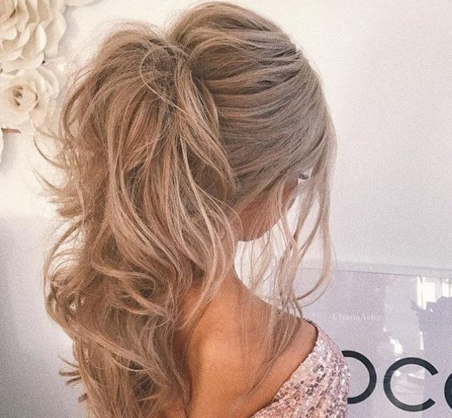 Coiffures de bal de fin d'année : gros plan d'une femme aux cheveux blonds cendrés ondulés, coiffée en queue de cheval bouffante, portant une robe rose à paillettes et posant dans une chambre
