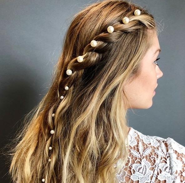 les coiffures de bal de fin d'année : gros plan d'une femme aux cheveux bruns avec une tresse d'accent accessoirisée, portant un haut à fleurs blanches et posant à l'extérieur