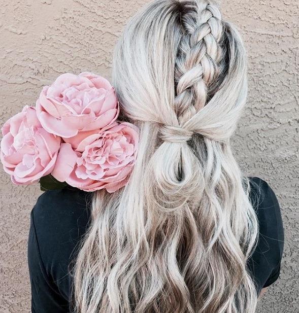 les coiffures de bal de fin d'année : gros plan d'une femme aux cheveux ondulés d'une blonde platine, façonnée en une tresse de licorne et une queue de cheval mi-haute, mi-bouclée, tenant des fleurs et posant sur un fond blanc