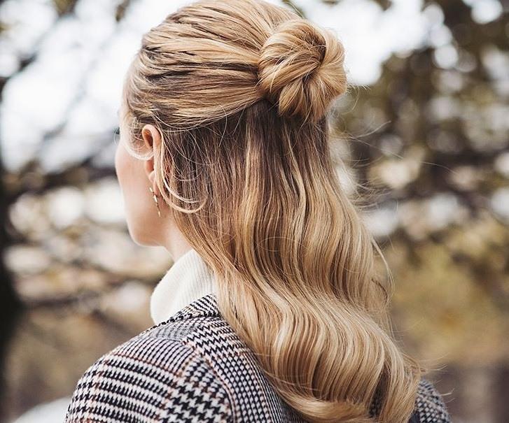 idées de coiffure pour le bal de fin d'année : plan rapproché d'une femme avec une coiffure en chignon mi-lisse mi-abondante, portant un blazer à carreaux et posant à l'extérieur
