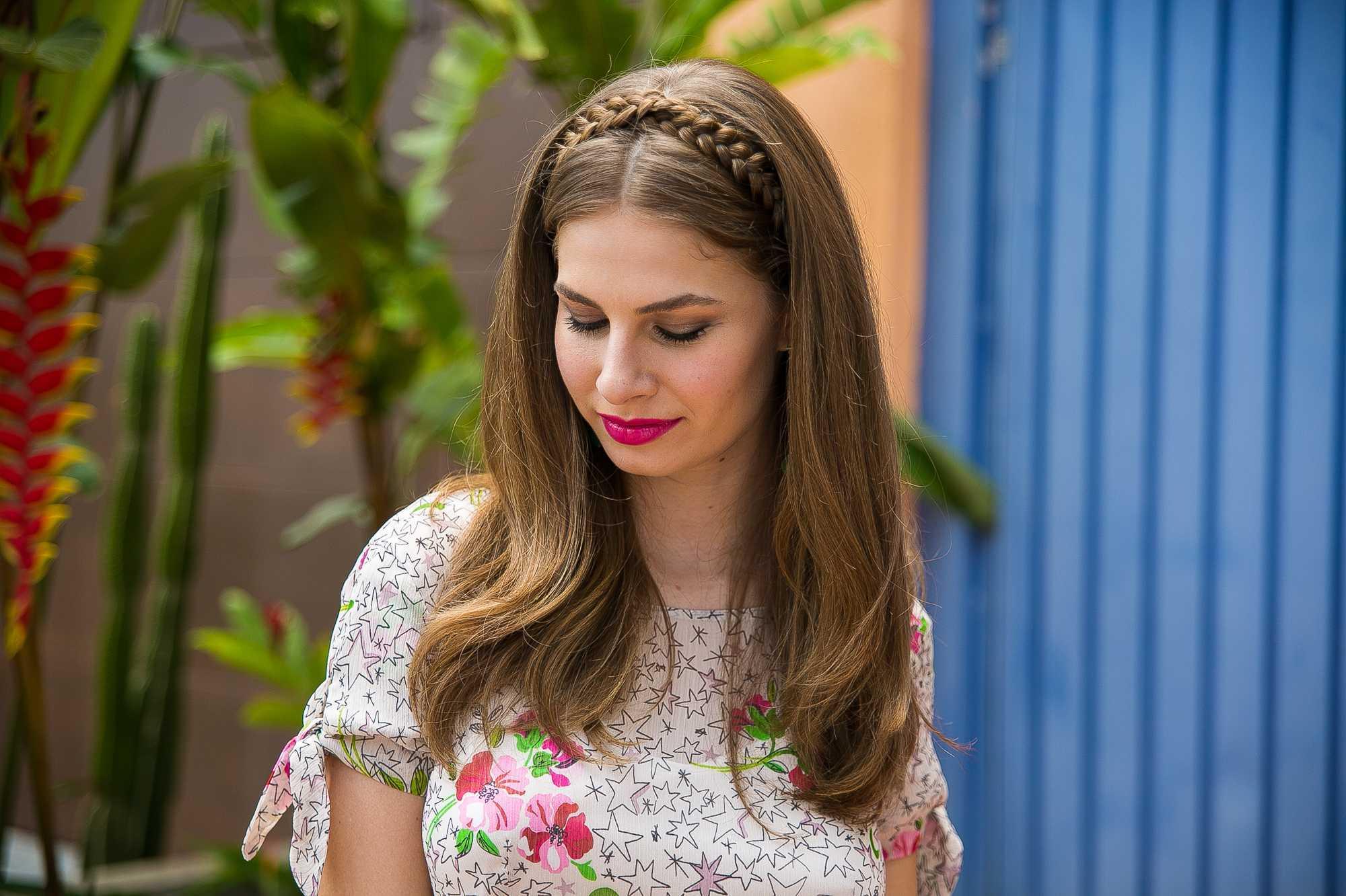 Coiffures de bal tressées : plan rapproché d'un mannequin avec des cheveux châtains moyens coiffés en vagues libres et un bandeau tressé, portant un top floral et posant à l'extérieur
