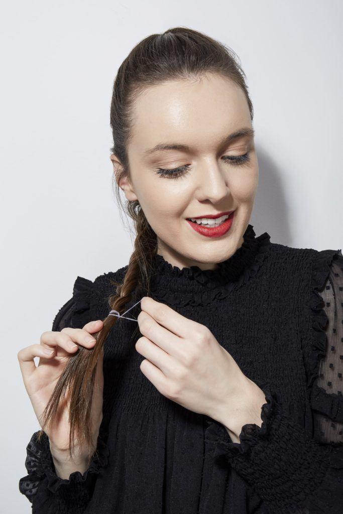 Comment tresser ses propres cheveux en France Fille brune qui noue sa tresse avec une cravate