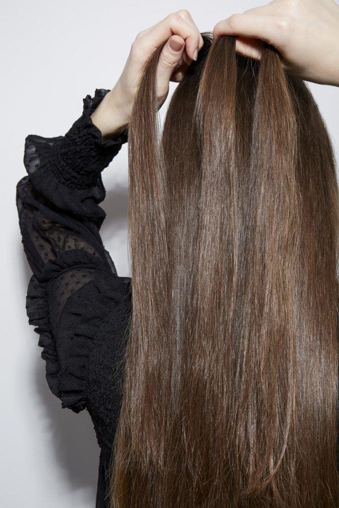 Comment tresser ses propres cheveux en France Une fille brune qui tresse ses cheveux