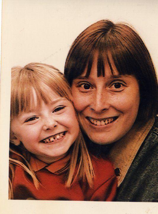 Photo de mère et de fille. Fille aux cheveux blonds et raides avec une frange et femme aux cheveux bruns avec une frange.