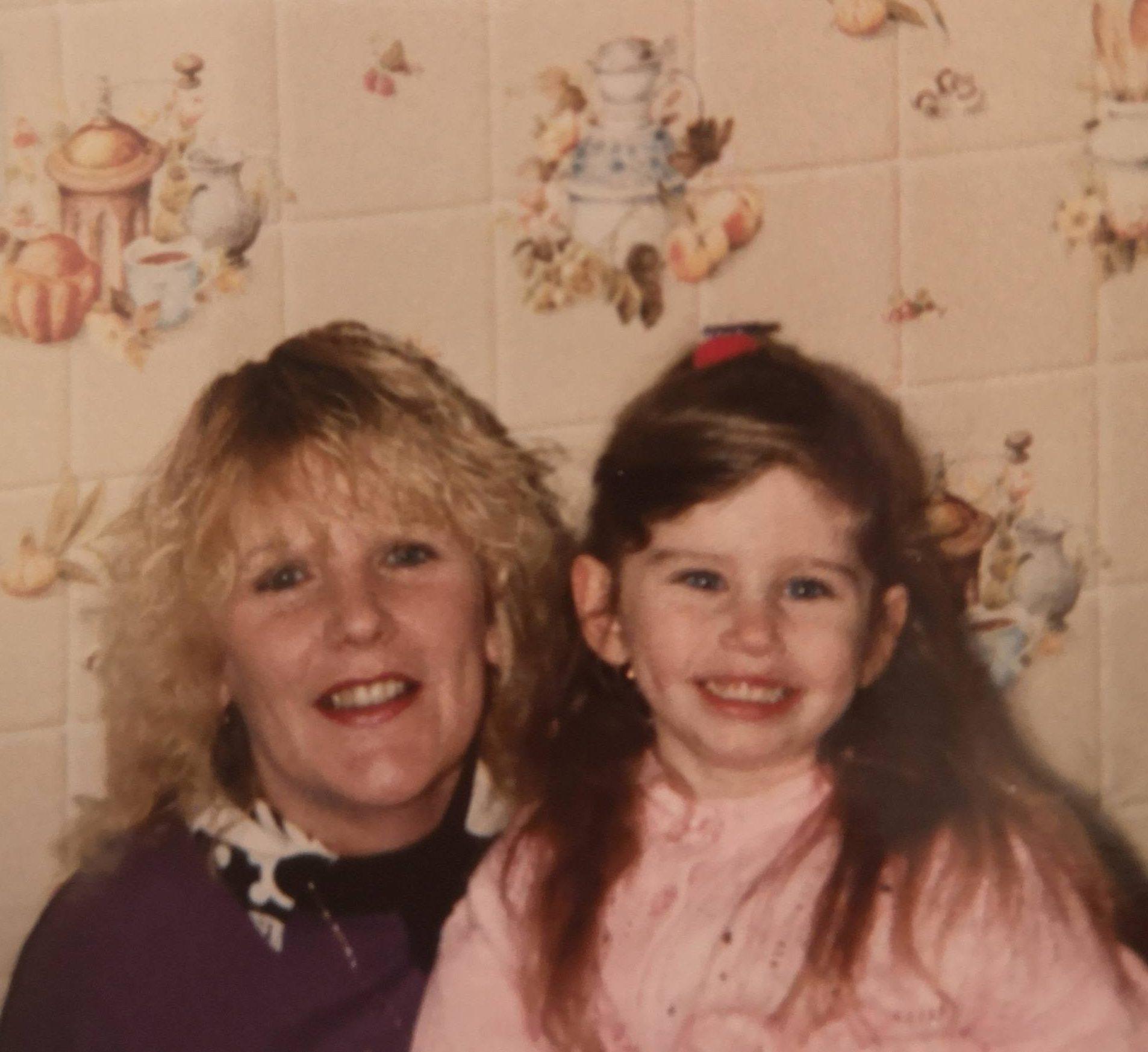 Photo d'une mère et de sa fille. Femme avec des cheveux blonds ondulés et fille avec une longue coiffure brune à moitié relevée.