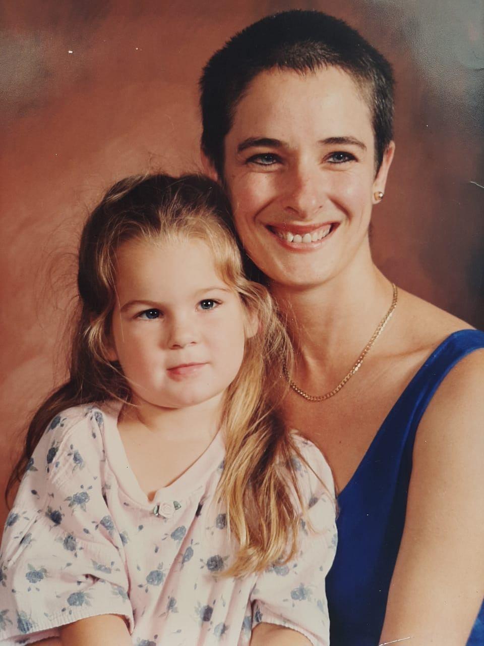 Photo d'une mère et de sa fille. Fille avec des cheveux blonds mi-hauts, mi-bas et femme avec des cheveux bruns courts.