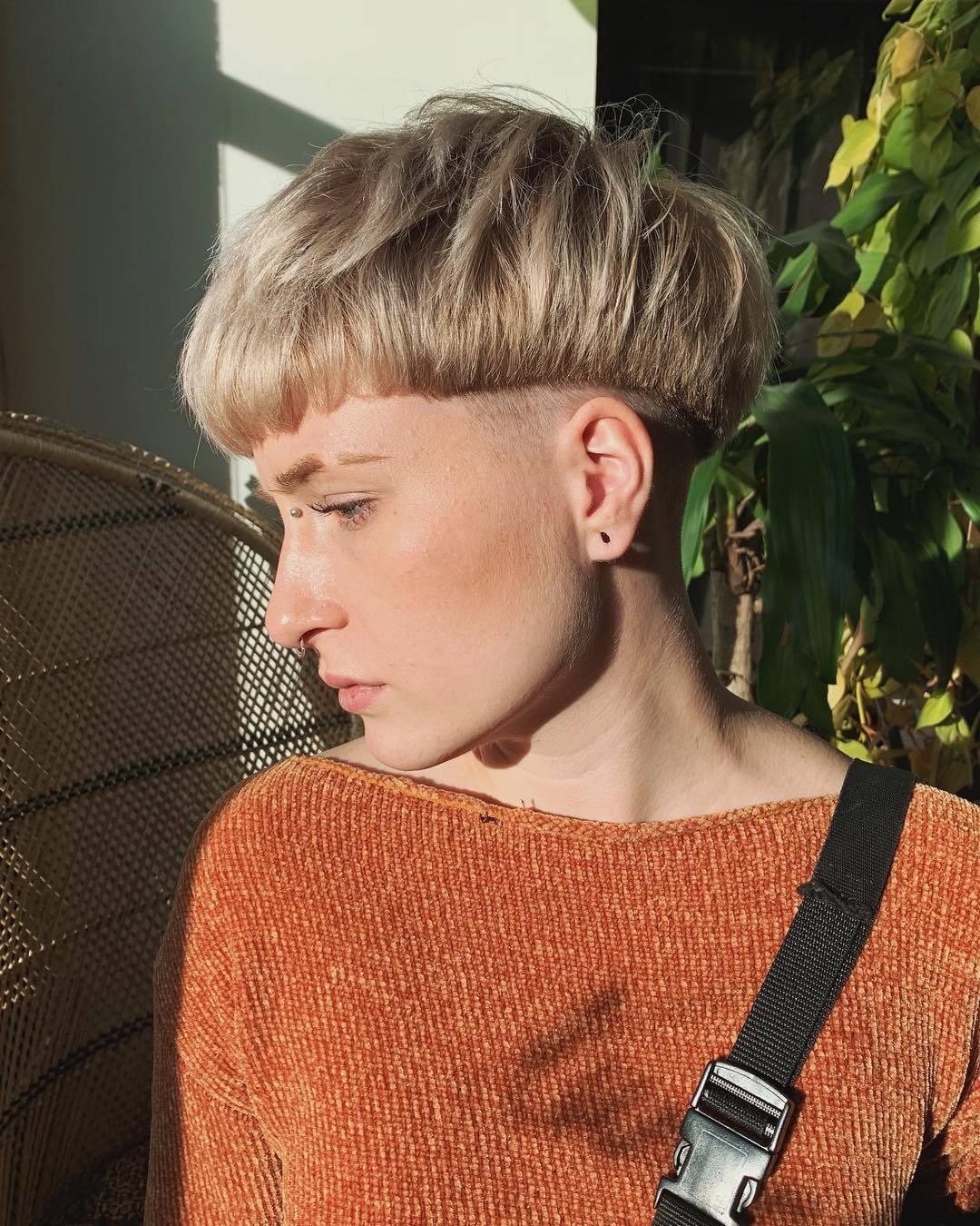 Femme avec une coupe de cheveux blonde en bol et une coupe de cheveux rasée en dessous.