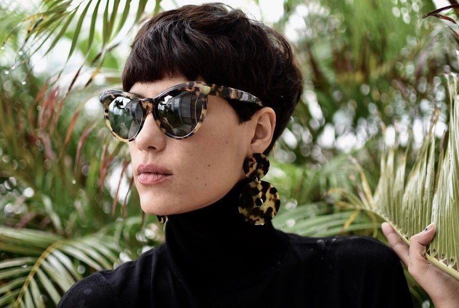 Femme avec une coupe de cheveux texturée et moderne, portant des lunettes de soleil.
