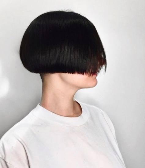 Vue de côté d'une femme aux cheveux noirs avec une coupe de cheveux en forme de champignon.