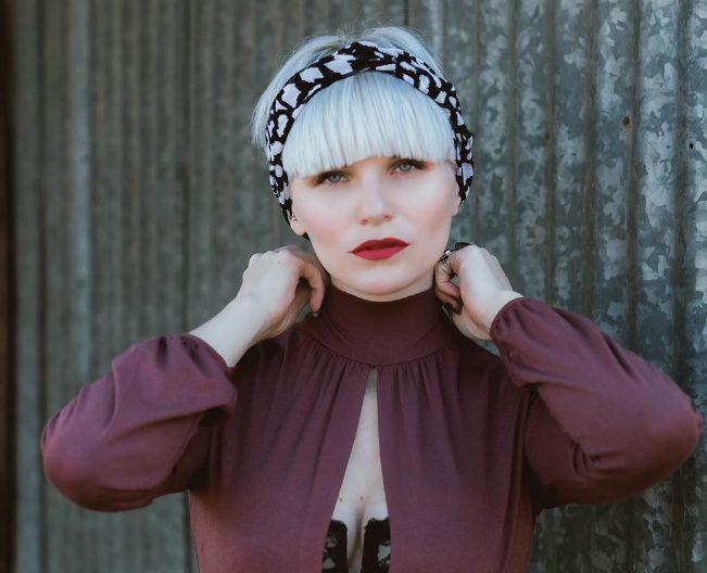 modèle avec une coupe de cheveux champignon avec un accessoire noir enroulé autour d'elle