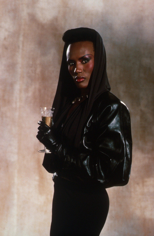 Cheveux des années 80 : Grace Jones cheveux naturels afro haut de gamme portant une capuche noire dans une image des années 80.
