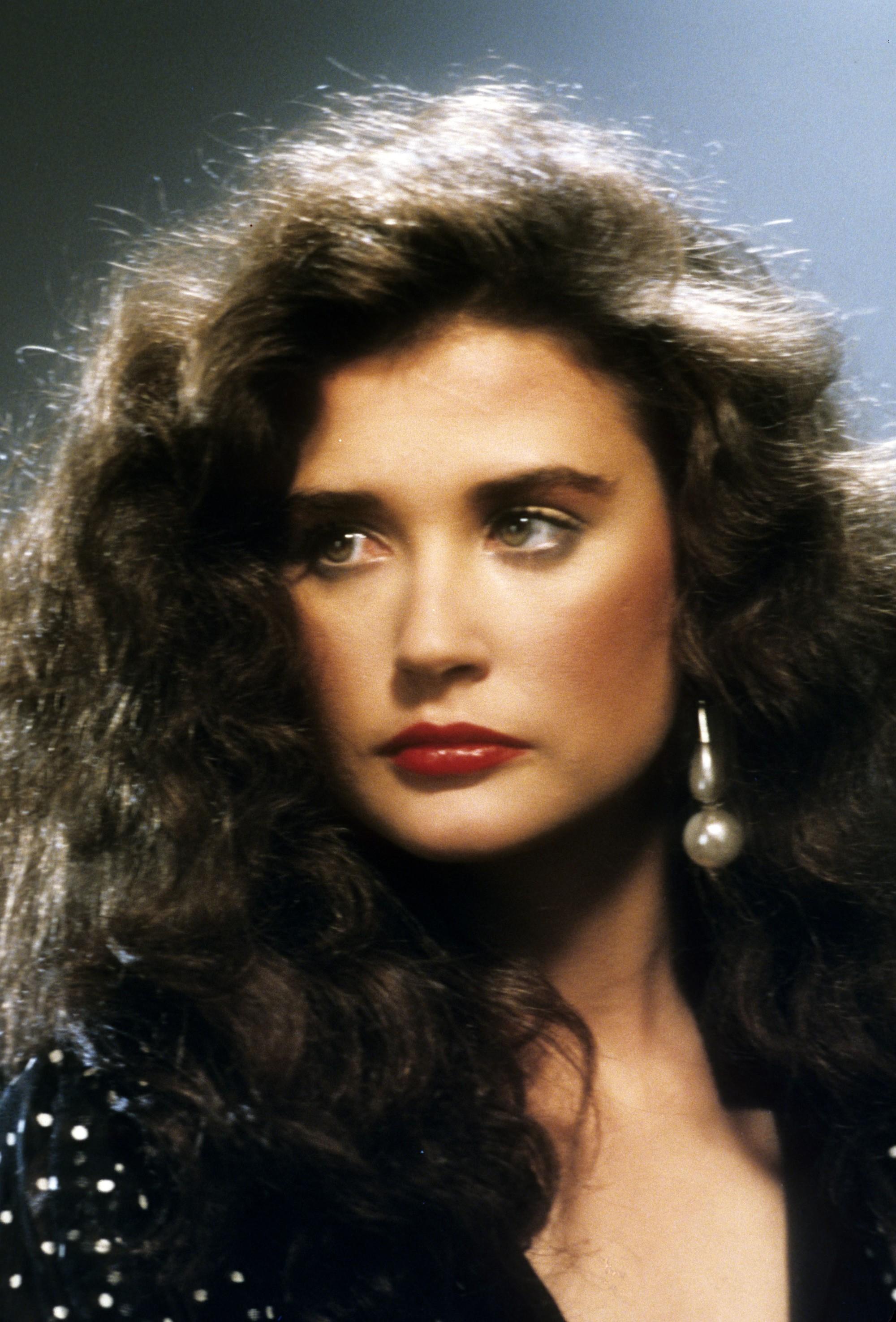 Coiffures des années 80 : Demi Moore jeune, cheveux bruns bouclés et ondulés des années 80, portant une boucle d'oreille en gros plan.