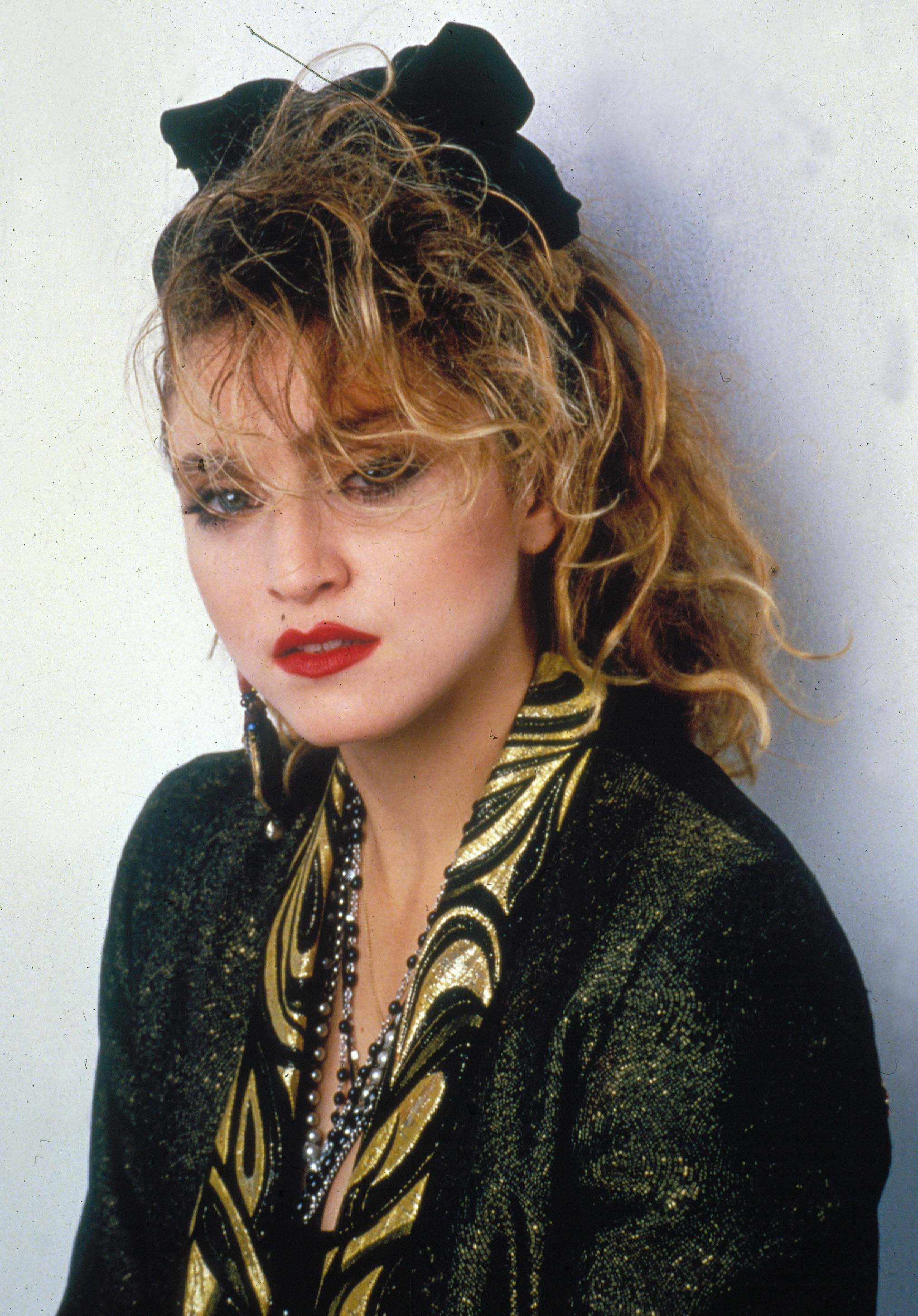 Coiffures des années 80 : Madonna avec une coiffure bouclée style années 80 avec un bandeau noir, portant une veste en cuir et un maquillage audacieux.