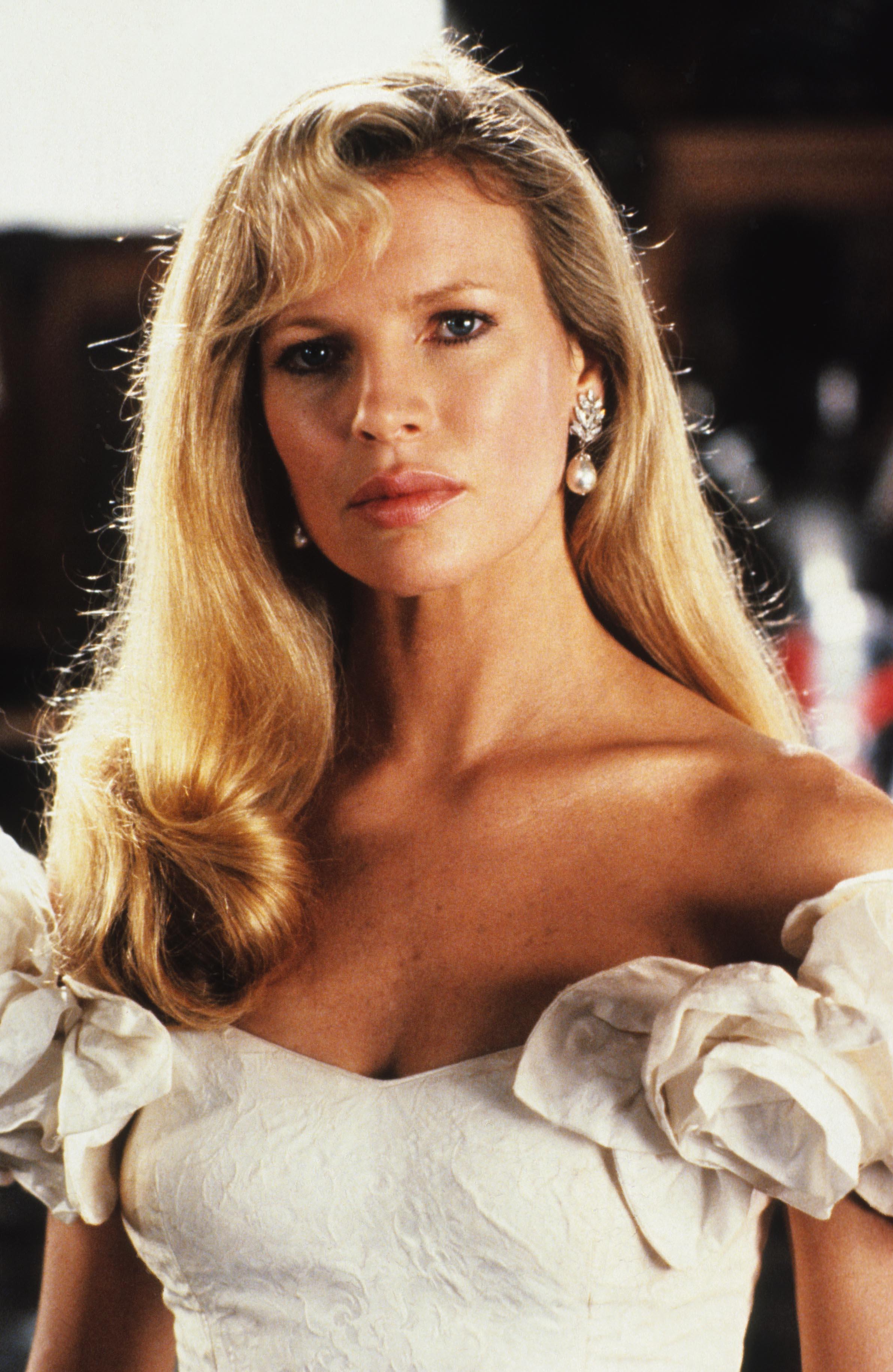 Coiffures des années 80 : Kim Basinger, longue chevelure blonde avec une raie sur le côté, style années 80, et une robe blanche décolletée.
