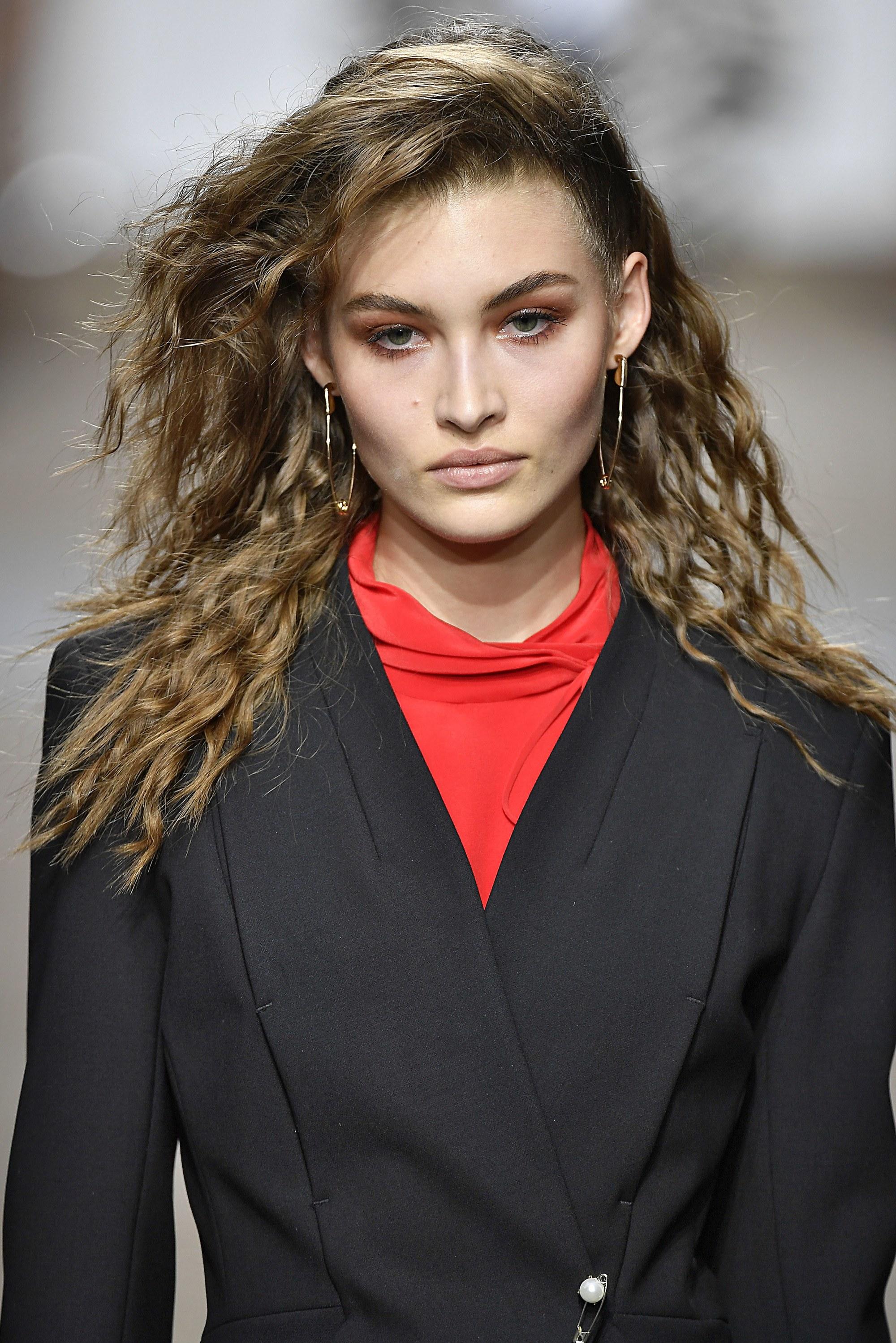 Coiffures des années 80 : modèle topshop aux cheveux longs bruns coiffés avec des vagues modernes des années 80 sur le podium