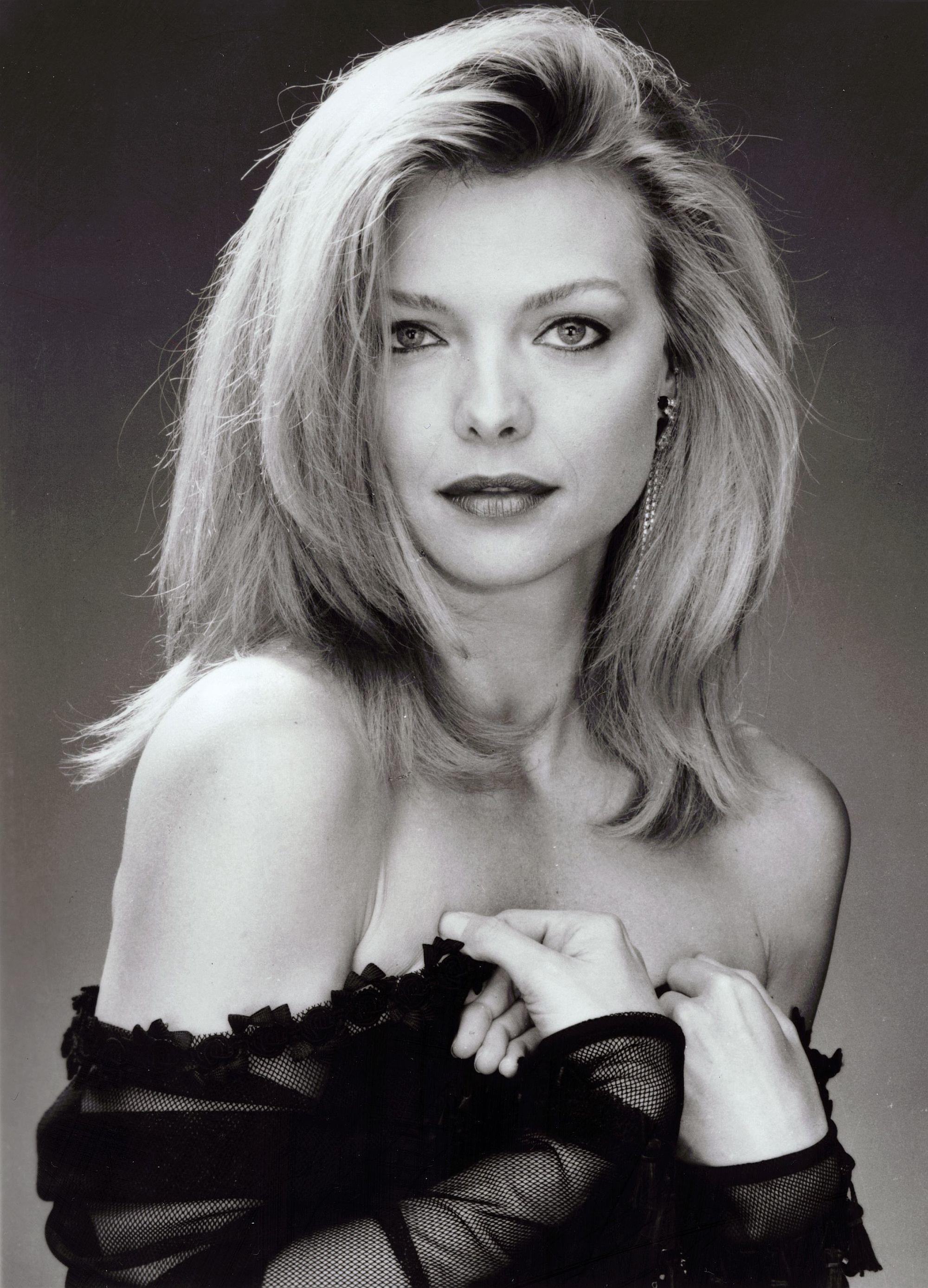 Coiffures des années 80 : Michelle Pfeiffer, cheveux blonds séchés au sèche-cheveux, longueur moyenne des épaules, raie sur le côté et robe à épaules dans une pose séduisante.