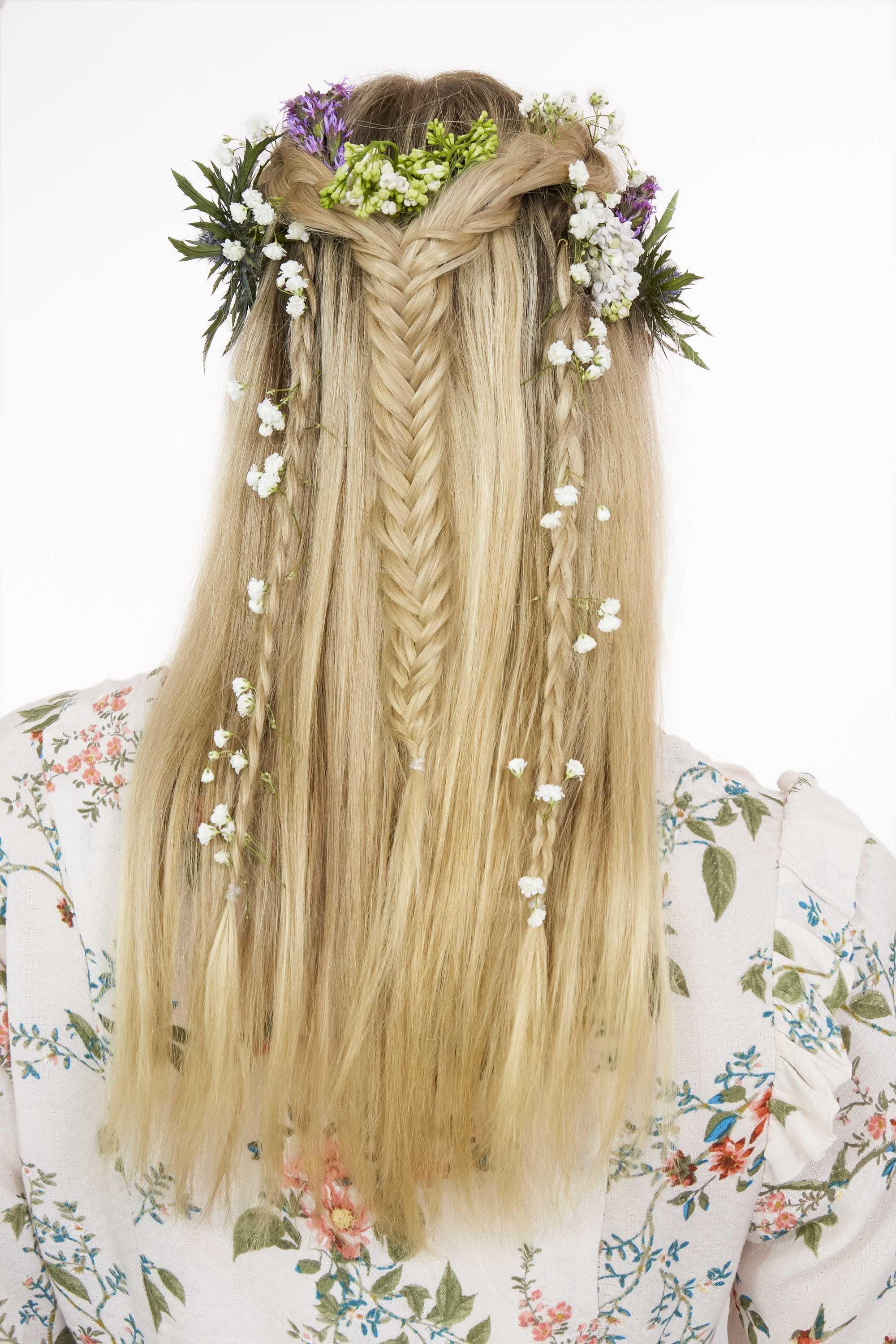 idées de cheveux pour le bal de fin d'année : gros plan d'une femme aux cheveux blonds dorés, coiffée en tresse en queue de poisson mi-haute, mi-basse, avec un mélange d'autres tresses, avec des fleurs tissées dedans, posant dans un décor de studio