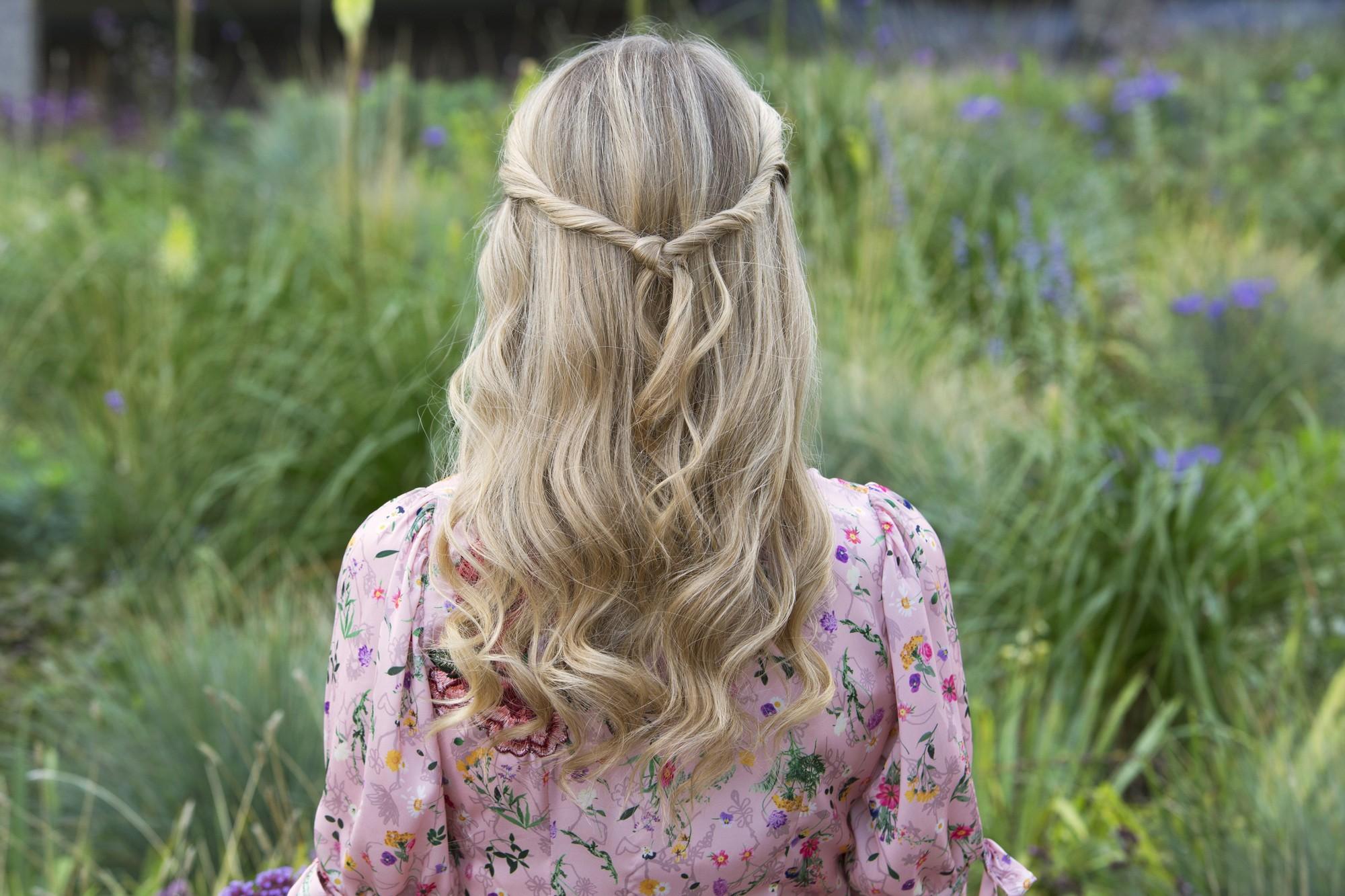 les coiffures de bal de fin d'année : gros plan arrière d'une femme aux cheveux blonds cendrés, portant une coiffure nouée mi-haute, mi-dessous, portant une robe florale rose et posant à l'extérieur