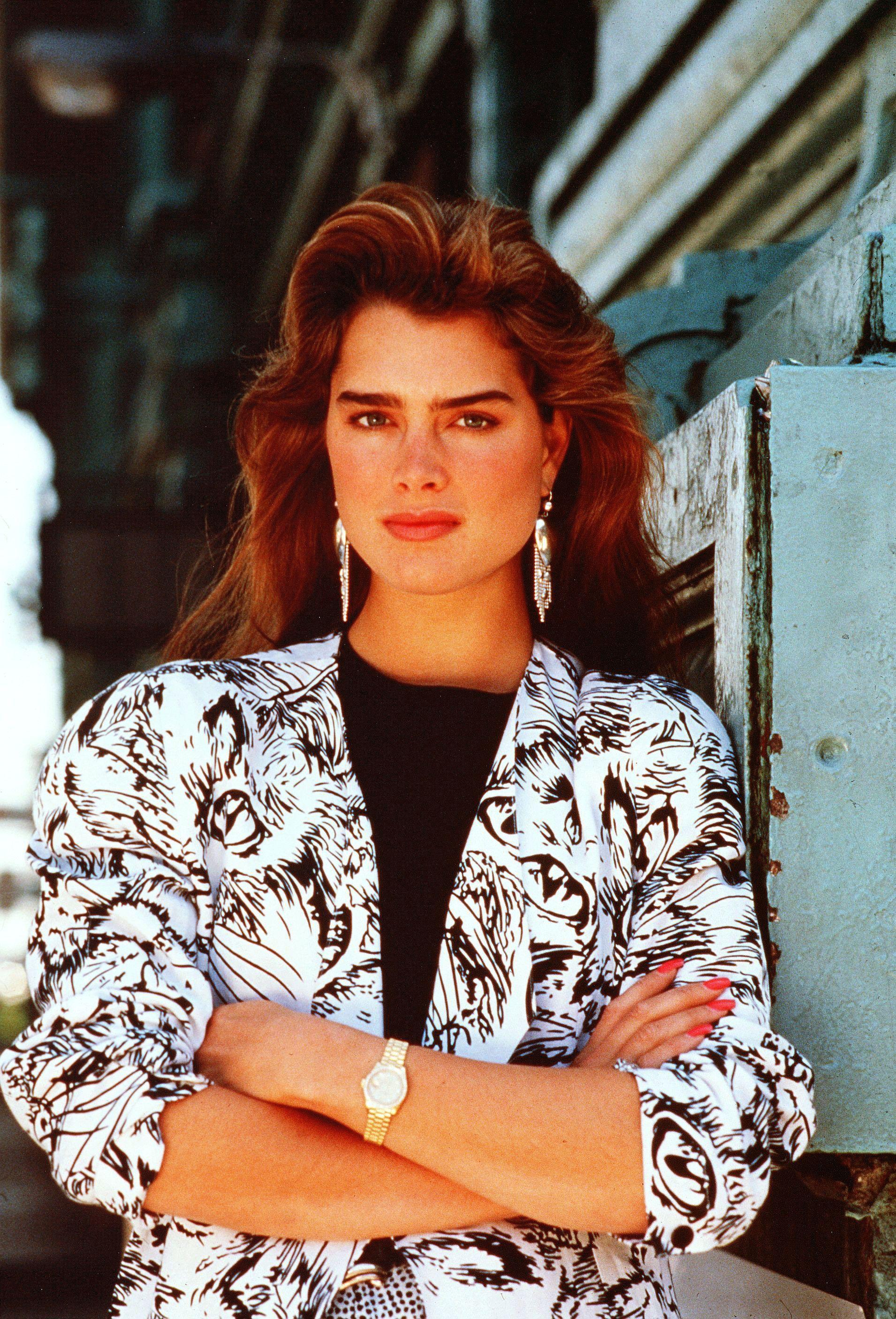 Coiffures des années 80 : La jeune Brooke Shields avec de gros cheveux bruns séchés au sèche-cheveux des années 80, portant un blazer à motifs et les bras croisés.